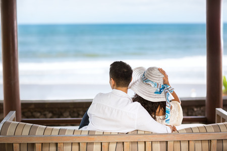 people relaxing: Embracing couple enjoying the view of the azure blue sea, back view Stock Photo