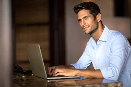 writer: Handsome man using laptop, pensively looking away