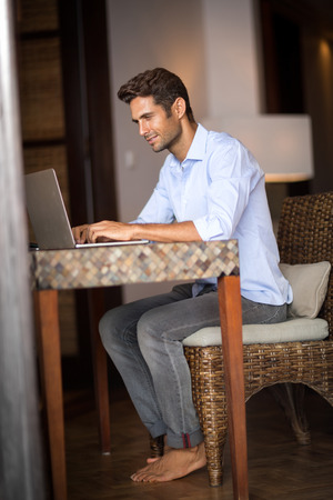 barefoot man: young guy sitting at home with barefoot on table, using laptop computer