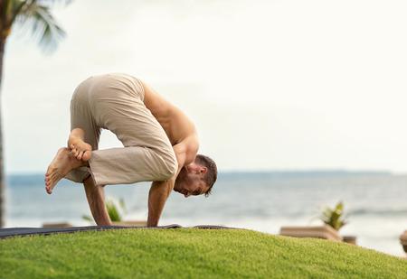 yoga man: Young man doing yoga on the beach near the ocean Stock Photo