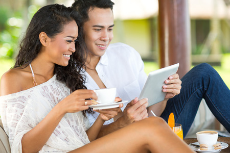 sexy couple on beach: Balinese couple enjoy in resort with tablet pc Stock Photo