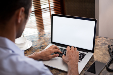 空の画面で探している彼のラップトップで作業する人