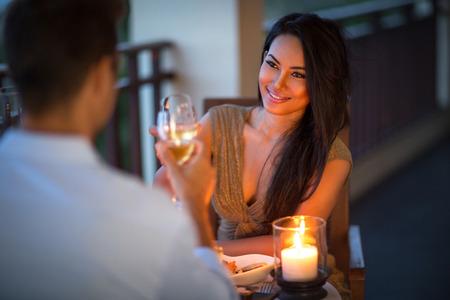 dattes: jeune couple avec un dîner romantique avec des bougies sur un balcon tropical Banque d'images