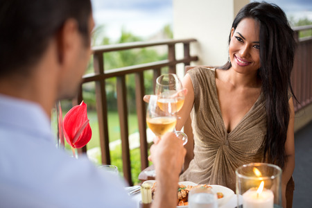 Young couple drinking wine ad toasting during romantic dinner photo