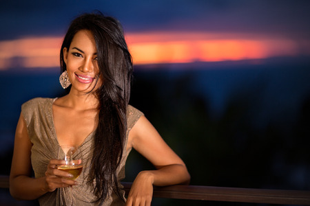 Beautiful woman with drink over sunset background in elegant dress photo