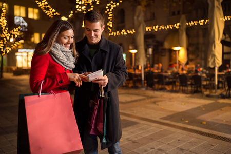 lifestyle shopping: Happy couple checking shopping list for Christmas on street Stock Photo