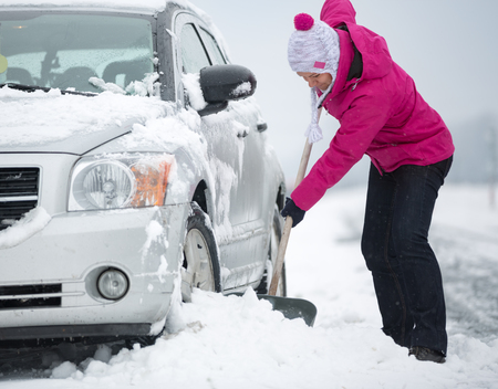stuck: woman with shovel clears snow around the car Stock Photo