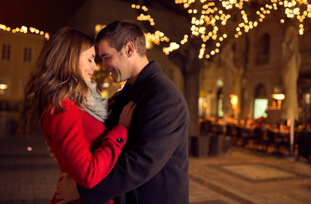 winter couple: Young happy attractive amorous couple embracing  and kissing outdoor
