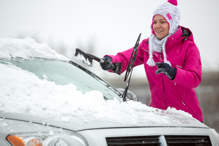 scraping: Woman cleaning car windshield of snow winter Stock Photo