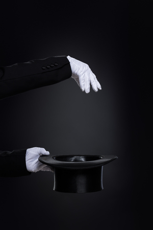 Magician?s hands in white gloves with top hat over black Stock Photo