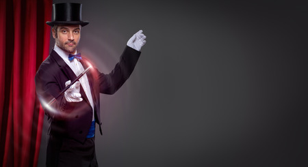 illusionist: Magician with  magic wand in action