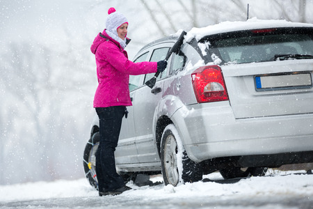 car exhaust: Woman cleaning her car from snow