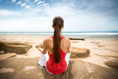 Peaceful woman meditating by ocean, back view