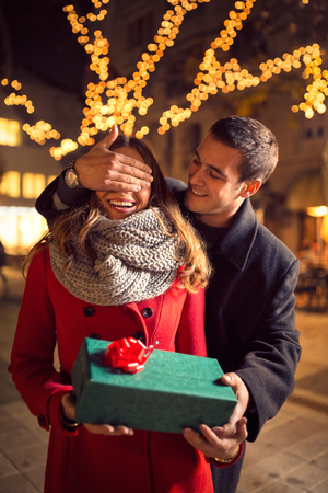 couple outdoor: romantic man covering his girlfriend s eyes, man standing behind woman with gift on street with Christmas decorated Stock Photo