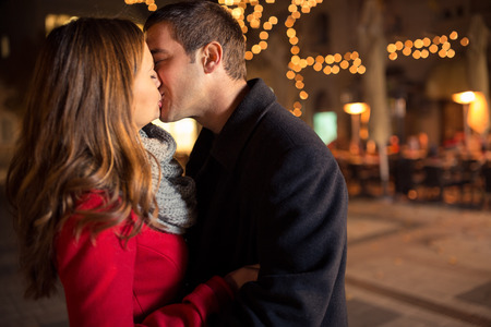 couple outdoor: Beautiful pretty girl kissing handsome boy on street with Christmas light in background Stock Photo
