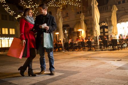 nacht: Fröhliche junge Menschen auf geschmückten Straße tun Weihnachtseinkäufe stehend