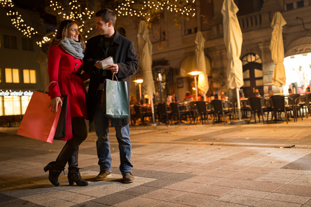 shopping: la gente joven alegre que hace compras que se coloca en la calle decorada de Navidad Foto de archivo