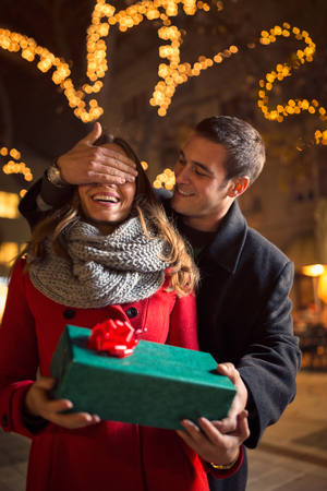 christmastime: Man surprising a woman with a gift on Christmastime