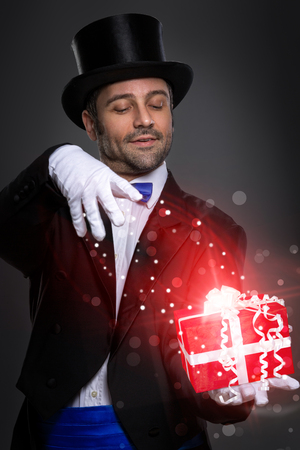 illusionist: magician performs the trick with magic gift
