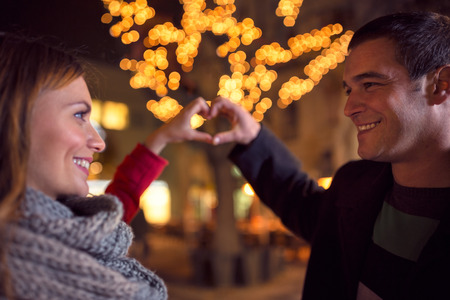 heart hands: Happy joyful couple on Christmastime at street  with heart sign making by their hands