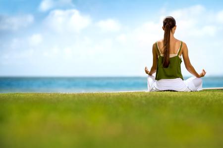 mujeres de espalda: Mujer que se sienta en el césped y haciendo yoga cerca del Océano