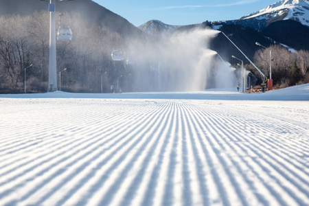 snow grooming machine: perfectly groomed empty ski run with snow cannon which is making powder snow