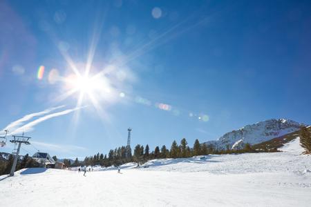 superficie: Snowy pista de esquí con brillante invierno soleado en el cielo