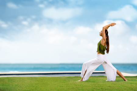 balance: Young woman practicing yoga with sea in background