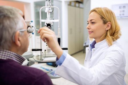 Joven médico ojo femenino determina ojos dioptrías usando instrumentos en la sala de consulta Foto de archivo - 52135815
