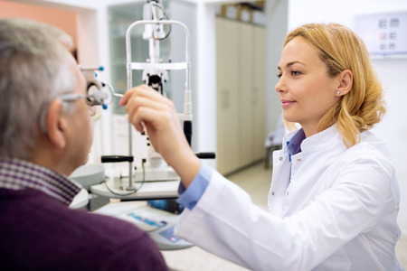 determines: Young female eye doctor determines eyes diopter using instruments in consulting room