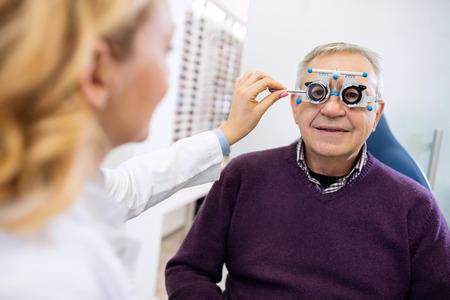 to examine: Male senior in eye clinic examine eyes