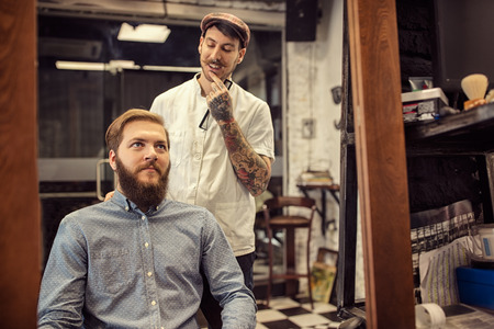 barber: Male barber giving client haircut in shop