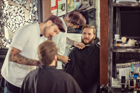 barber scissors: man barber with scissors cut the beard smiling client