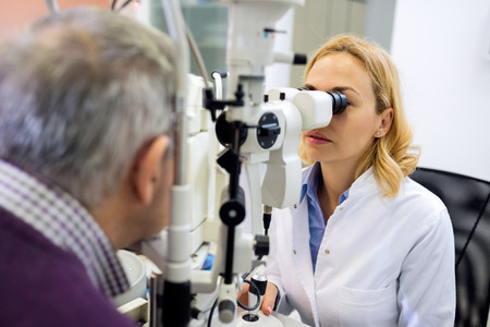 Patient eye doctor checkup patient eyes with apparatus Stock Photo