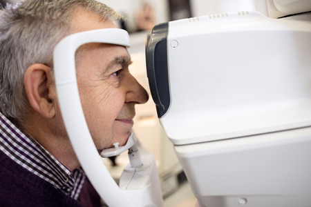 Close up of senior check his sight using apparatus at eye clinic