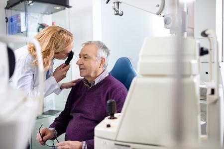 oftalmólogo femenina determina dióptrico para hombre de edad avanzada Foto de archivo