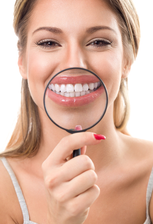 white face: Beautiful woman with magnifying glass showing her perfect white teeth