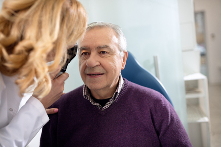 Senior looks in instrument for checking eyes at ophthalmologist