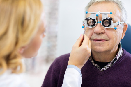 Optical specialists precisely determines diopter to senior male patient in clinic