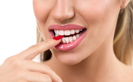 finger licking: Sexy woman mouth with finger between tooth over white background Stock Photo