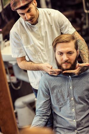 skillful: skillful barber making haircut too bearded customer at barbershop