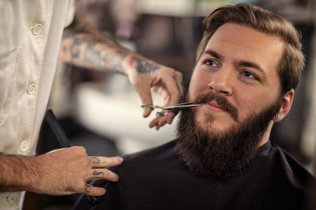 hombre del peluquero con las tijeras cortó el cliente bigote sonriente