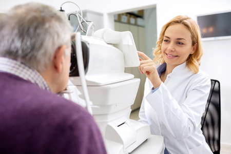 ambulant: Young female eye doctor work with patient using eyes apparatus