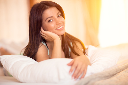 rested: Young girl posing in the morning on the pillow in her bed Stock Photo