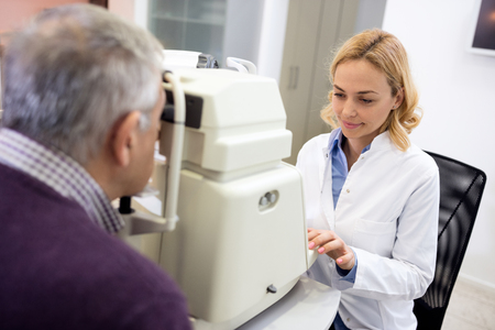 determines: Nice female eye specialists determines diopter using apparatus in clinic Stock Photo