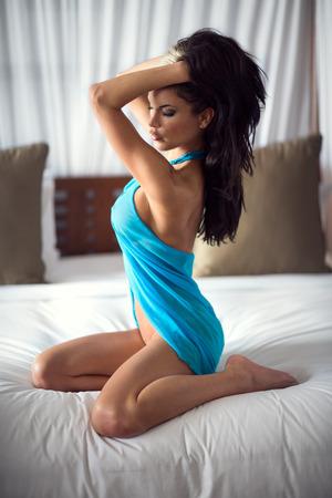 mujer sexy desnuda: joven y bella mujer en la cama en bufanda azul Foto de archivo