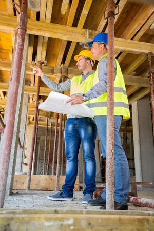 Supervisor de la obra de construcción con el arquitecto mirando acumulen en el sitio de construcción