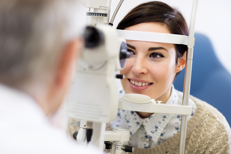 diopter: Dark hear woman look in ophthalmoscope to determine diopter in clinic Stock Photo