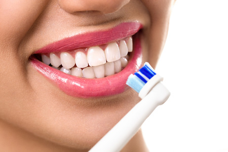 tooth whitening: Close up of perfect and healthy teeth with electric toothbrush