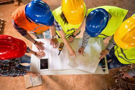 Top view of group of architects and engineers checking blue print if construction is going as planned Archivio Fotografico